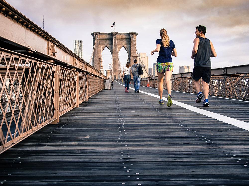 a couple going for a run across the Brooklyn Bridge