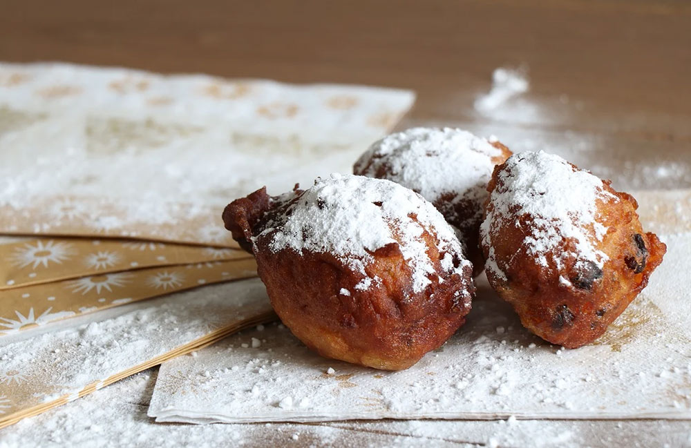 3 oliebollen with powdered sugar