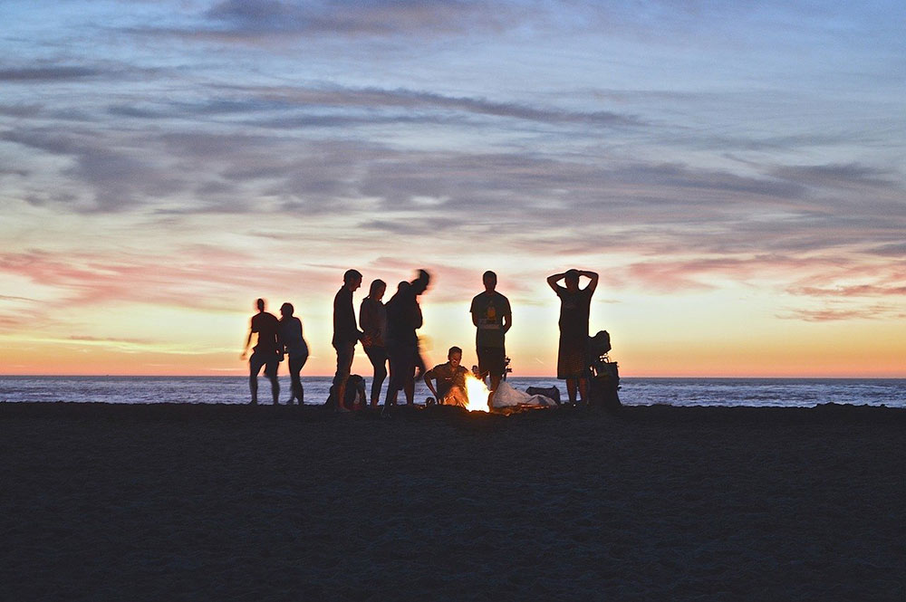 a group of people on the beach at sunset