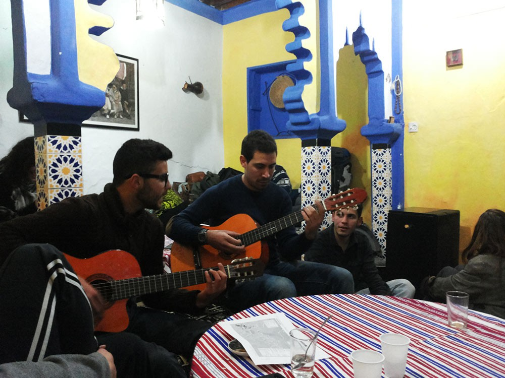 2 guys playing the guitar at a hostel in Morocco