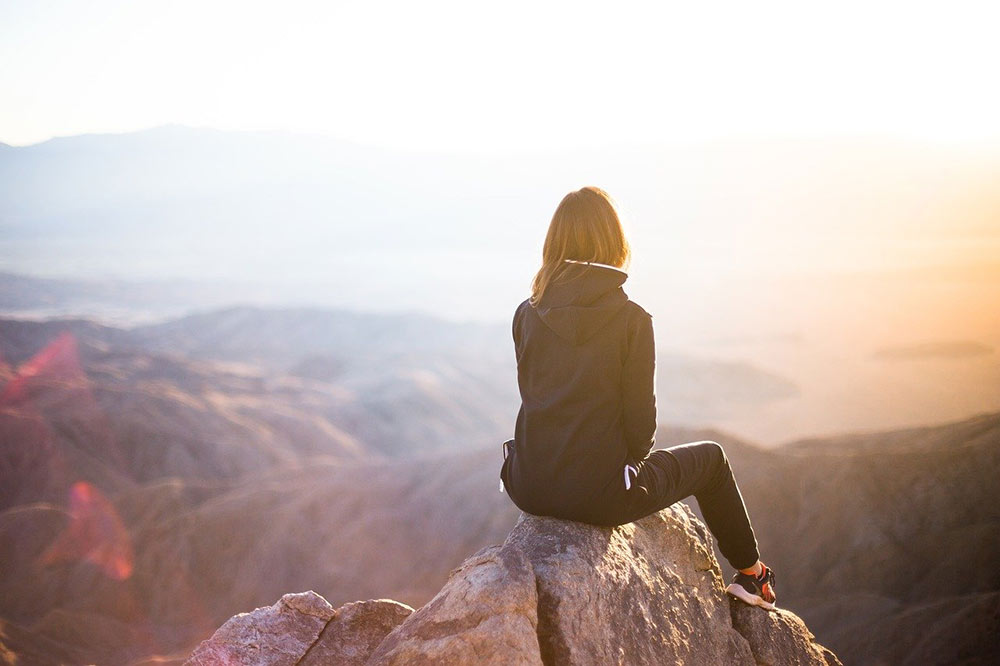 a woman contemplating reasons to travel