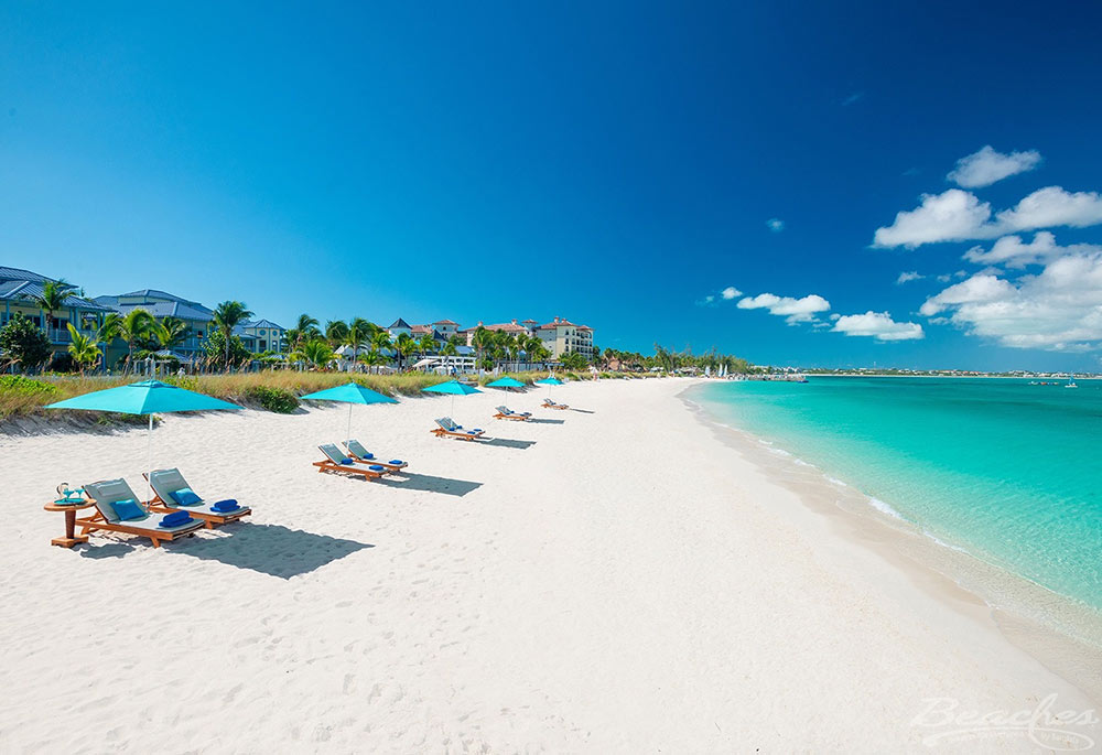 the beach in front of a luxury villa in Turks and Caicos