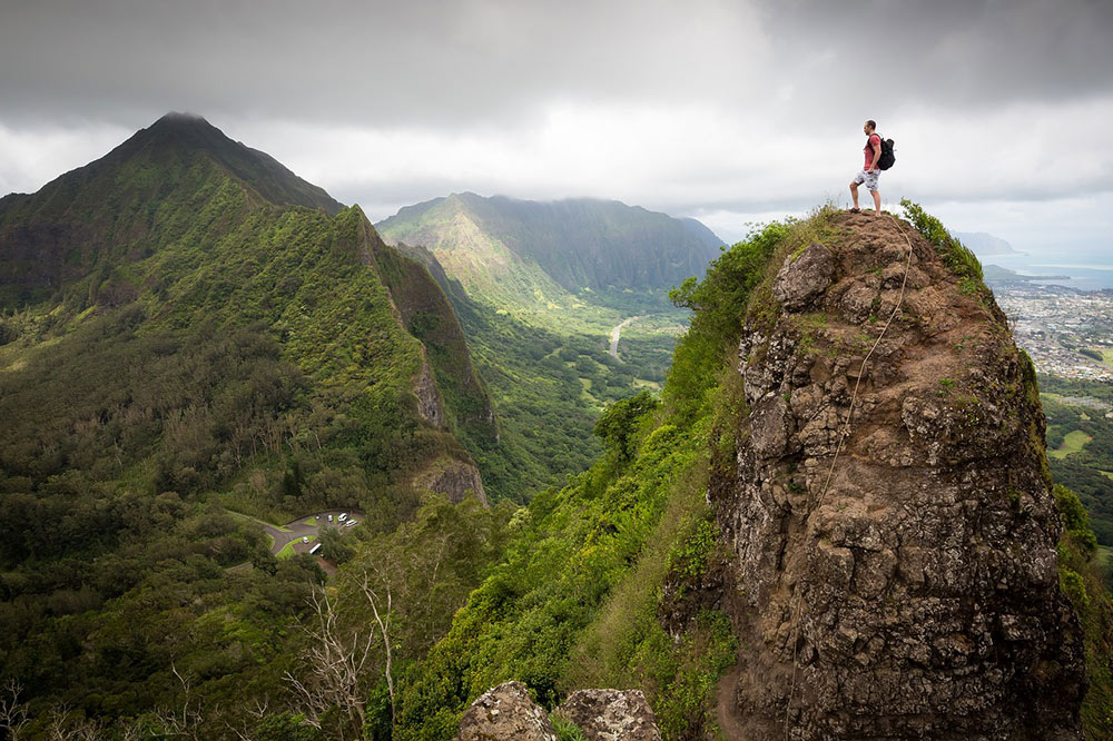 a man who hiked to the top of a mountain on a cloudy day