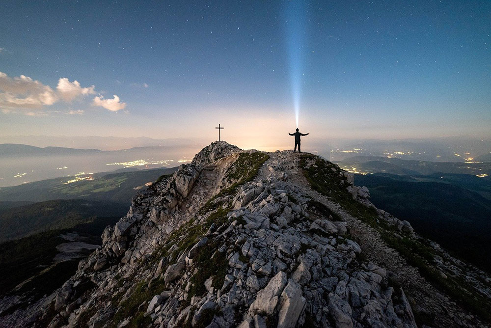a guy shining his headlamp on top of a mountain