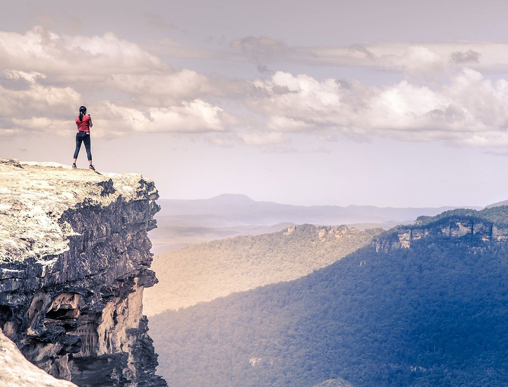 a woman hiking to the top of a cliff